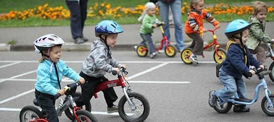 дети едут на беговелах